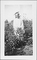 [Young woman in white graduation gown standing in flower garden, Rohwer, Arkansas, 1942-1945]