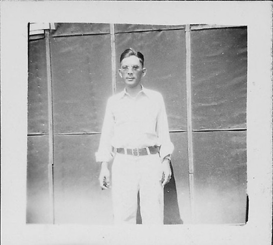 man in glasses standing in front of tarpapered barracks