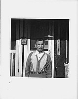 [Mustached older man in eyeglasses in front of mailbox and door, Rohwer, Arkansas, 1942-1945]