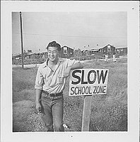 "[Smiling man in eyeglasses leaning against ""Slow School Zone"" sign, Rohwer, Arkansas, October 12, 1944]"