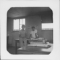 [Boy and man at K. Tasugi's desk, Rohwer, Arkansas, 1942-1945]
