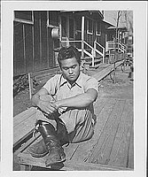 [Young man sitting on deck, Rohwer, Arkansas, February 18, 1945]