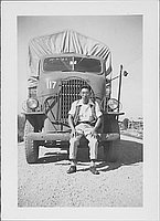 [Young man in vest sitting on front bumper of transport vehicle, Rohwer, Arkansas, October 10, 1944]