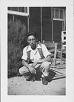 [Young man in vest crouching with cigarette, Rohwer, Arkansas, October 10, 1944]