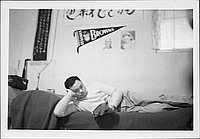 [Man reclining on bed reading a magazine below St. Louis Browns pennant, Rohwer, Arakansas, November 9, 1944]