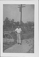 [Man standing next to wooden bridge and utility pole, Rohwer, Arkansas, October 12, 1944]