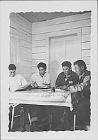 [Four young men seated around table, Rohwer, Arkansas]