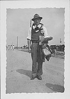 [Man in hat and leis standing on dirt road, Rohwer, Arkansas, 1943]