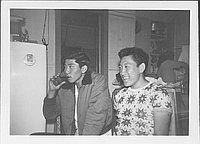 [Two young men, one drinking from glass, in a kitchen, United States, 1948]