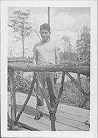 [Man in t-shirt and jeans on wooden bridge, Rohwer, Arkansas, 1942-1945]