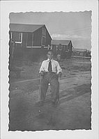 [Man sitting in chair in open area in front of barracks, Rohwer, Arkansas, July 7, 1944]