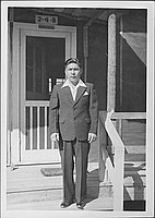 [Man in suit standing on porch steps of barracks, 2-4-B, Rohwer, Arkansas, 1942-1945]
