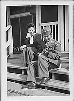 [United States Army soldier playing ukulele next to woman on barrack steps, Rohwer, Arkansas, February 11, 1945]