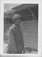 [United States Army soldier in combat uniform and eyeglasses in front of buildings]