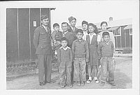 [Two United States Army soldiers with large family in front of barracks, Rohwer, Arkansas, November 21, 1944]