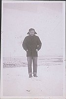 [Portrait of man in black coat standing in snow, Heart Mountain, Wyoming, Winter 1944-1945]
