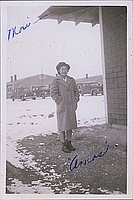 [Portrait of a young woman in overcoat with cars in background, Heart Mountain, Wyoming, Winter 1944-1945]