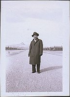 [Portrait of man in hat and coat standing in middle of road with Heart Mountain in background, Wyoming, 1945]