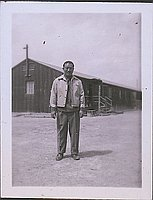 [Portrait of Man standing in front of barracks, Heart Mountain, Wyoming, 1945]
