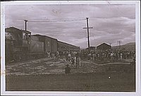 [Large group of people gathered next to a train, Heart Mountain, Wyoming, 1945]