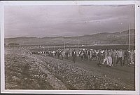 [Large crowd of people walking up road, Heart Mountain, Wyoming, 1945]
