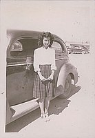 [Young woman in plaid skirt standing in front of car, Heart Mountain, Wyoming, 1942-1945]