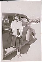[Young woman with bow in hair standing in front of car, Heart Mountain, Wyoming, ca. 1942-1945]