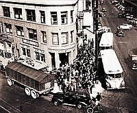 [Aerial perspective of crowd boarding buses in front of Nishi Hongwanji Buddhist Temple, Los Angeles, California, 1942]