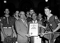 "[Los Angeles City Councilman Gilbert Lindsay presenting ""Boy Scout International Day"" proclamation to Boy Scouts, Los Angeles, California, July 28, 1970]"