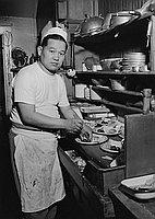 [Cook preparing food at Daruma Cafe, Los Angeles, California, April 5, 1955]