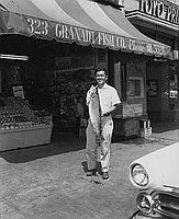 [Larry Nitta holding trout in front of Granada Fish Company, Los Angeles, California, July, 1, 1956]