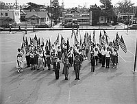 [Girl and Boy scouts holding American flags in Hobart Boulevard School yard, Los Angeles, California, May 2, 1957]
