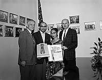 [George F. Robinson of Modern Shoe Repair receives special Los Angeles City Council resolution in the office of councilman Gordon Hahn, Los Angeles City Hall, Los Angeles, California, December 19, 1957]