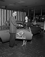 [Caucasian man handing a key to a woman in front of car at Ford Hermosa Beach, California, 1957]