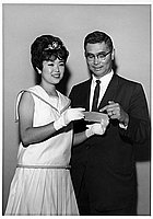 [Nisei Week Princess Betty Taira receives donation from Mr. Omatsu of Downtown JACL at Toyo Miyatake Studio, Los Angeles, California, August 1963]