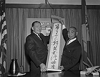 [Sekke Ogomori presents calligraphy scroll to Los Angeles Mayor Sam Yorty at Los Angeles City Hall, Los Angeles, California, August 1963]