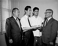 [Nichoren giving money for Pasadena Buddhist Church cooking exhibition at Japanese Chamber of Commerce office, Los Angeles, California, January 17, 1966]
