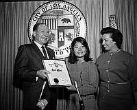 "[Los Angeles Mayor Sam Yorty presenting ""Girl's Week"" proclamation to a young Japanese American woman at City Hall, Los Angeles, California, 1966]"