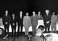 [Men of different ethnicities standing in front of curtained stage, California, 1966?]