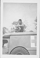 [Man sitting on roof of Red Cross vehicle, Rohwer, Arkansas, November 2, 1944]