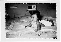 [Smiling infant lying on bedspread, Rohwer, Arkansas, July 29, 1944]