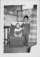 [Toddler in sailor outfit sitting on chair next to boy in suit, Rohwer Arkansas, May 24, 1944]