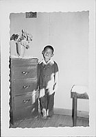 [Smiling boy in suit next to chest of drawers, Rohwer, Arkansas, May 24, 1944]