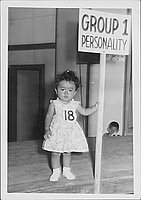 "[Toddler in floral dress with sign, ""Group 1 personality"", Rohwer, Arkansas, July 6, 1944]"