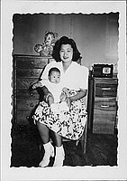[Woman in floral skirt holding infant in her lap, Rohwer, Arkansas]