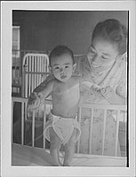 [Infant standing in crib holding woman's hands, Rohwer, Arkansas]