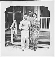 [Three people in front of barracks porch, Rohwer, Arkansas]