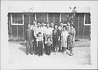 [Group portrait of eleven adults and two boys in front of barracks, Rohwer, Arkansas]