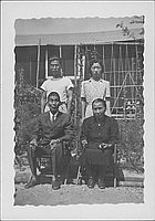 [Seated elderly couple with young man and woman in front of barracks, Rohwer, Arkansas]