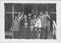 [Eleven adults and children on barracks porch steps, portrait, Rohwer, Arkansas]